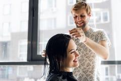 Lachende en meisje en kapper die terwijl het maken van een nieuw kapsel of een kapsel spreken glimlachen stock afbeelding