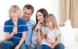 Lachende Familie, die zusammen singt Stockbild