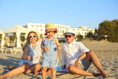 Lachende Familie mit Vater, Mutter, Töchter, die Picknick am Strand haben stockbild