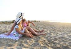Lachende Familie mit Vater, Mutter, Töchter, die Picknick am Strand haben lizenzfreie stockfotos