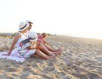 Lachende Familie mit Vater, Mutter, Töchter, die Picknick am Strand haben lizenzfreie stockbilder