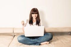 Lachende Frau, die auf dem Sofa sitzt Stockfotografie