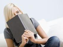 Lachende Frau, die ein Buch anhält Stockfotos