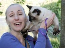Lachende Frau, die eine junge Katze in ihren Armen in einem Sommerpark hält stockbild