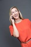 Lachende Frau, die an ihrem Handy plaudert Lizenzfreie Stockfotografie