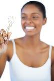 Lachende Frau, die ihren Wimperlockenwickler betrachtet Stockbild