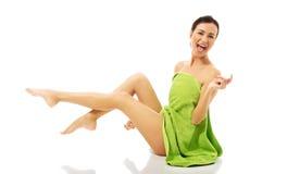 Lachende Frau eingewickelt im Tuch mit den Beinen oben Lizenzfreies Stockbild