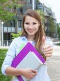 Lachende Frau mit dem langen blonden Haar auf dem Campus, das Daumen zeigt Lizenzfreie Stockfotos