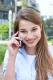 Lachende Frau mit dem langen blonden Haar, das draußen am Telefon spricht Stockfoto