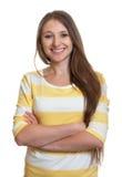 Lachende Frau mit dem langen braunen Haar und den gekreuzten Armen Stockbilder
