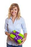 Lachende Frau mit gelocktem blondes Haar- und Weihnachtsgeschenk Lizenzfreie Stockfotografie