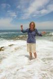 Lachende Frau steht in Meerwelle Schaumgummi stockfotos
