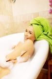 Lachende Frau in voller Länge, die im Bad sich entspannt Stockbild