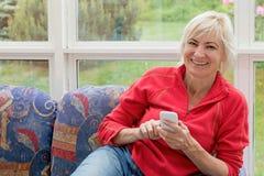 Lachende Frau von mittlerem Alter mit einem Handy in ihren Händen Lizenzfreies Stockbild