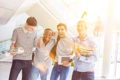Lachende Freunde in der Universität Stockbilder