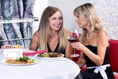 Lachende Freunde, die zu Abend essen stockbilder