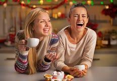 Lachende Freundinnen, die Weihnachtssnäcke essen Stockbild