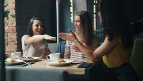Lachende Freundinnen, die zusammen Hände in das Café genießt Freundschaft einsetzen stock video footage