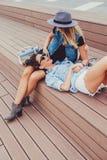 Lachende Freundinnen während Klatsch draußen auf der Treppe lizenzfreie stockfotos
