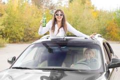 Lachende gedronken vrouwelijke autopassagier stock foto's