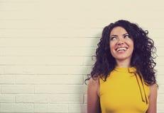 Lachende gelukkige die vrouw, op bakstenen muurachtergrond wordt geïsoleerd stock foto's