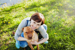 Lachende gelukkige jonge vrouw die in denimoverall haar rode leuke hond Shar Pei in het groene gras in zonnige dag koesteren, war stock afbeelding