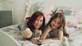 Lachende gelukkige moeder en leuke dochter die op grappige beeldverhaalfilm op TV letten terwijl het liggen op bed thuis in de oc stock footage