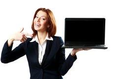 Lachende Geschäftsfrau, die Laptop hält und auf ihn zeigt Stockfotografie