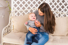 Lachende Gesichter der glücklichen Familie, entzückendes Kinderbaby haltene, lächelnde und umarmende Mutter, gesundes Kinderfrohe Stockbilder