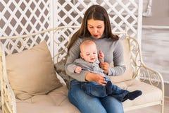Lachende Gesichter der glücklichen Familie, entzückendes Kinderbaby haltene, lächelnde und umarmende Mutter, gesundes Kinderfrohe Lizenzfreies Stockbild