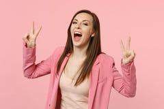 Lachende grappige jonge vrouw in jasje die mond brede die open houden, tonend overwinningsgebaar op pastelkleur roze muur wordt g royalty-vrije stock afbeelding