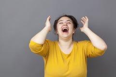 Lachende große Frau 20s, die Spaßsieg ausdrückt Stockfoto