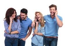 Lachende Gruppe zufällige Leute, die am Telefon sprechen Lizenzfreie Stockfotos