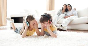 Lachende hörende Musik der Kinder mit Kopfhörern Lizenzfreies Stockfoto