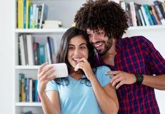 Lachende Hippie-Liebespaare, die Clip mit Telefon strömen lizenzfreies stockfoto