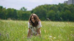 Lachende jonge donkerbruine vrouw op groen grasgebied, die zich op haar knieënhanden bevinden stock footage