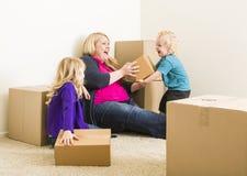 Lachende Jonge Familie in het Lege Zaal Spelen met het Bewegen van Dozen Stock Fotografie