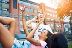 Lachende jonge meisjes die op een bank buiten het nemen van selfi liggen stock afbeeldingen