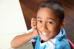 Lachende jonge schooljongen 9 die aan zijn klaslokaal zit Stock Foto