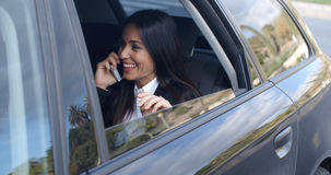 Lachende jonge stafmedewerker op telefoon in auto Royalty-vrije Stock Foto's