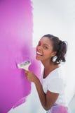 Lachende jonge vrouw die haar muur in roze schilderen Stock Foto