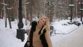 Lachende jonge vrouw die pret in de winterpark hebben stock video