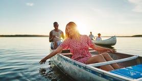Lachende jonge vrouw die pret met vrienden in een meer hebben stock afbeeldingen
