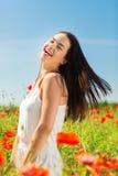 Lachende jonge vrouw op papavergebied Stock Fotografie