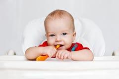 Lachende jongen die een lepel houden Stock Foto's