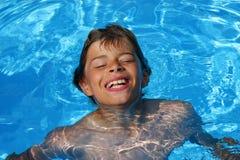 Lachende jongen die pret in zwembad heeft Stock Afbeelding