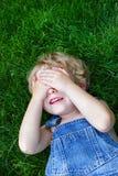 Lachende jongen die zijn ogen behandelt Stock Foto