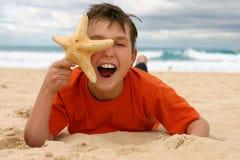 Lachende jongen met zeester op het strand stock afbeeldingen
