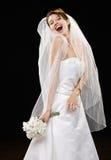 Lachende junge Braut im Hochzeitskleid und -schleier Lizenzfreies Stockfoto