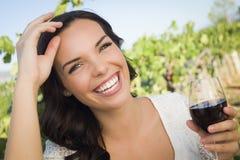 Lachende junge erwachsene Frau, die ein Glas Wein im Weinberg genießt Lizenzfreie Stockfotografie